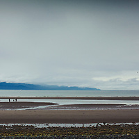 alaska, small figures walk on a beach in summer with grey clouds and distant mountains