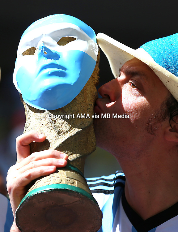 A Fan of Argentina kisses a replica world Cup trophy which has an Argentina mask on