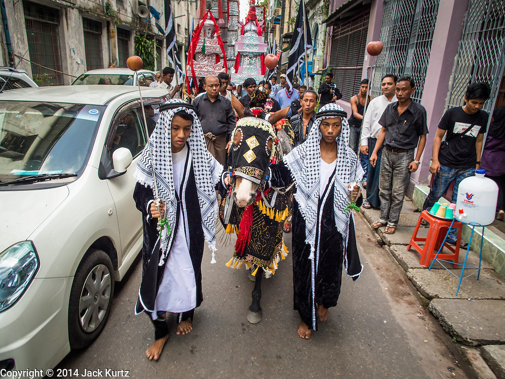 03 NOVEMBER 2014 - YANGON, MYANMAR: Shia Muslims lead a horse that represents Hussein bin Ali's horse through Yangon Monday. Shias in Yangon started the celebration of Ashura Monday. Ashura commemorates the death of Hussein ibn Ali, the grandson of the Prophet Muhammed, in the 7th century. Hussein ibn Ali is considered by Shia Muslims to be the third Imam and the rightful successor of Muhammed. He was killed at the Battle of Karbala in 610 CE on the 10th day of Muharram, the first month of the Islamic calendar. According to Myanmar government statistics, only about 4% of Myanmar is Muslim. Many Muslims have fled Myanmar in recent years because of violence directed against Burmese Muslims by Buddhist nationalists.    PHOTO BY JACK KURTZ
