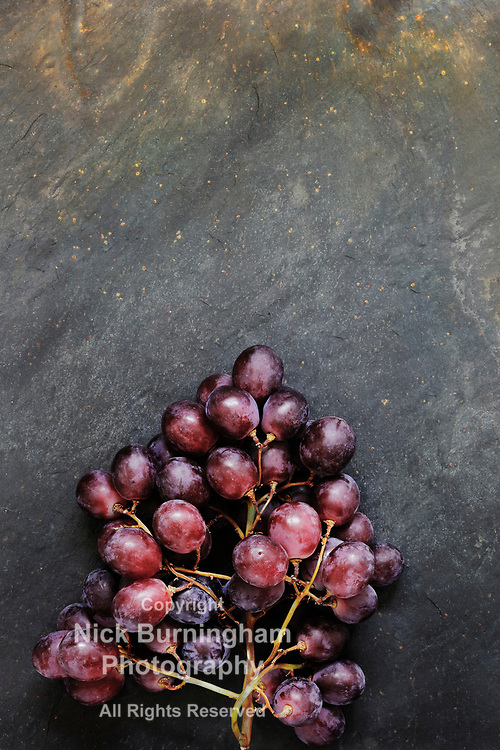 Dark Food - Fresh unpolished dark red black grapes on black slate stone background with copy space above