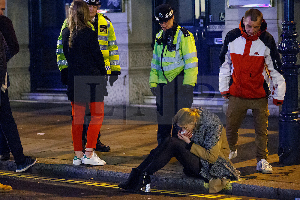 © Licensed to London News Pictures. 01/01/2017. London, UK. A reveller feels unwell as people celebrate the New Year in central London during the first hours of 2017 on January 1. Photo credit: Tolga Akmen/LNP
