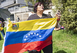 April 30, 2019 - Bogota, Colombia - A woman holds a Venezuelan flag in front of the consulate in Bogota, Colombia, on 30 April 2019  because of the crisis in her country and in support of the interim president, Juan Guaido  (Credit Image: © Daniel Garzon Herazo/NurPhoto via ZUMA Press)