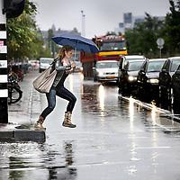 Nederland, Amsterdam , 12 juli 2012..Door de heftige regenval vanmorgen kwamen verschillende straten en wegen in de stad blank te staan van het overtollige water zoals hier op de Piet Heinkade....Foto:Jean-Pierre Jans