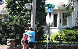 August 2, 2017 - Minneapolis, Minnesota, U.S. - Family members hug under a street sign near the site of an explosion and building collapse at Minnehaha Academy on Wednesday. One person was killed and one is unaccounted for in an explosion at the Minnehaha Academy upper school, officials said. Nine were injured, and three of them are in critical condition. (Credit Image: © David Joles/TNS via ZUMA Wire)