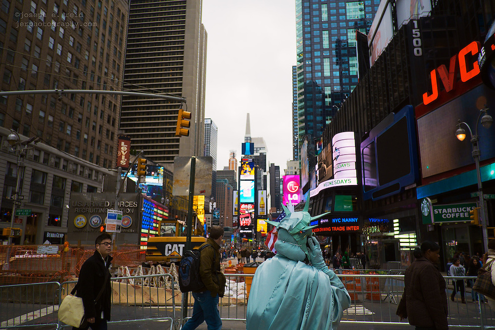 Human Statue of Liberty on cell phone in Times Square the day before Hurricane Sandy was to hit New York
