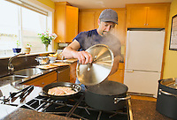 Middle aged man cooking in his home.