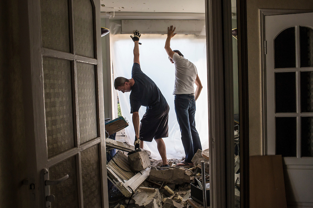 Men use plastic to seal off a wall which was destroyed when the apartment building was hit by a suspected grad rocket strike on Tuesday, July 29, 2014 in Donetsk, Ukraine.