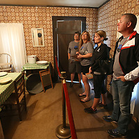 A group of bicyclists travling across the country on their way to Washington DC for National Police Week, view the small kitchen space of Elvis's childhood home as they tour the Elvis Presley Birthplace on Thursday afternoon.