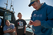 Roger Blackstone, right, shows Zachary Dickson, left, and Matt Stephenson how to use a herring bait to catch chinook salmon on Lake Coeur d'Alene on Saturday as a part of Free Fishing Day.
