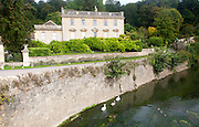 River Frome and the classical Georgian facade of Iford Manor, near Freshford, Wiltshire, England, UK