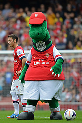 Arsenal's Mesut Ozil walks passed the Arsenal Mascot - Photo mandatory by-line: Mitchell Gunn/JMP - Tel: Mobile: 07966 386802 22/09/2013 - SPORT - FOOTBALL - Emirates Stadium - London - Arsenal V Stoke City - Barclays Premier League