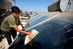 INDIA MUMBAI 29MAY10 - Housekeeper Narayan Bahadur (28) cleans solar thermal panels for a hot water installation on a roof of an apartment block in Juhu, Mumbai, India...jre/Photo by Jiri Rezac / The Climate Group..© Jiri Rezac 2010