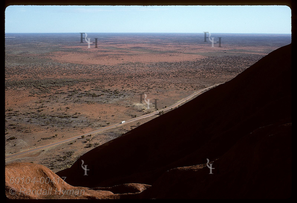 Sandstone slants sharply down to highway below in view from atop Ayers Rock on a summer morn Australia