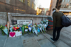 © Licensed to London News Pictures. 02/12/2019. London, UK. Commuters walk past flower on London Bridge. Two victims were died following a terrorist attack near London Bridge on 29th November when police shot dead the attacker. Photo credit: Vickie Flores/LNP