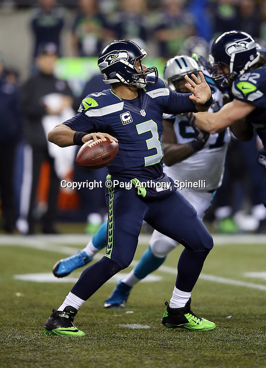 Seattle Seahawks quarterback Russell Wilson (3) throws a 63 yard touchdown pass for a 14-7 second quarter Seahawks lead during the NFL week 19 NFC Divisional Playoff football game against the Carolina Panthers on Saturday, Jan. 10, 2015 in Seattle. The Seahawks won the game 31-17. ©Paul Anthony Spinelli