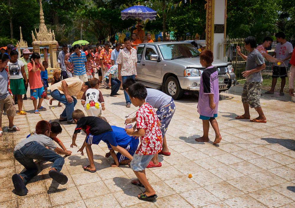 Children scramble to pick up good luck trinkets thrown by monks Songkran in Rural Thailand 2016