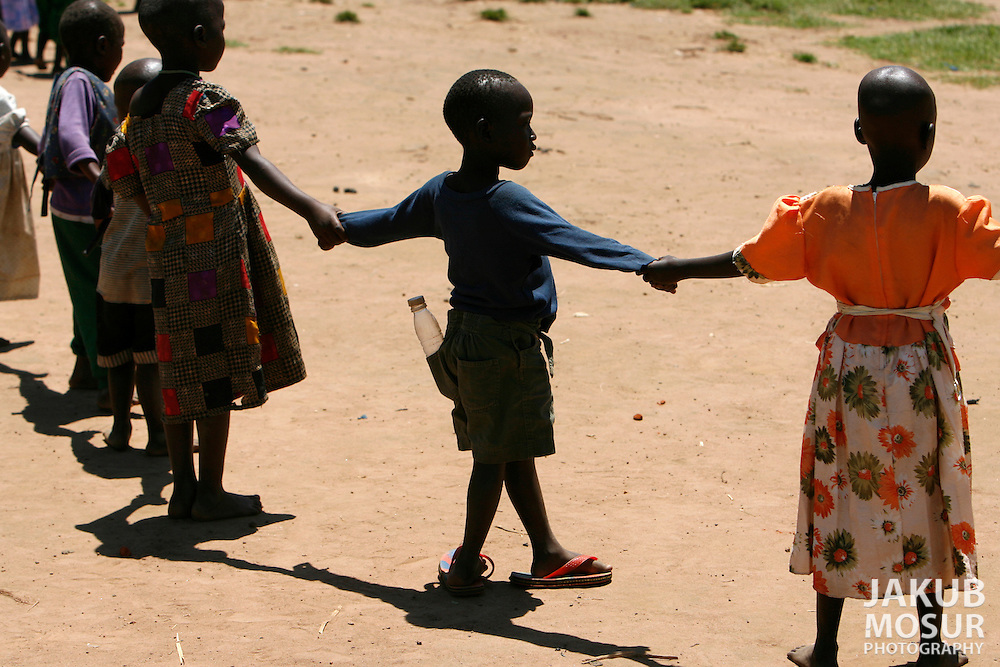 October 6, 2006 - Children dance in a circle at a day care center in Coope camp for internally displaced people, or IDP, near Gulu in north Uganda. Coope, with a population of 18,000, is one of 76 IDP camps around Gulu, the main base for the Uganda Peoples Defense Force fighting the insurgent Joseph Kony's Lord's Resistance Army. Kony's LRA movement has been fighting for the past 20 years to force the East African country to be ruled according to the Christian Ten Commandments. Over 2 million people, mostly of the Acholi tribe, have moved or were forced to move from their villages to camps close to the towns of Gulu, Lira, and Kitgum where they are watched over by the Ugandan Army. The LRA rebels have abducted thousands of children and have forced them to fight against the Ugandan Army and the Acholi people. Current peace talks between Kony's LRA and the Ugandan government held in Juba, southern Sudan, offer a glimpse of hope to ending this ongoing conflict..(Photo by Jakub Mosur/Polaris)<br />