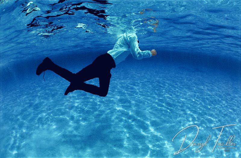 Fully clothed man swims with shoes in deep water.