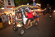 A decorated golf cart rides down Duval Street during Fantasy Fest halloween parade in Key West, Florida.