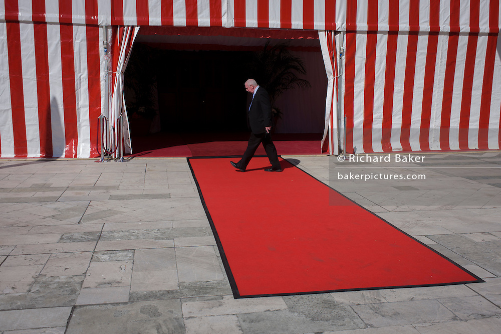 A Corporation worker inspects the red carpet and red and white striped marquee after a military event at the Guildhall in the City of London, the capital's financial district and historic heart.