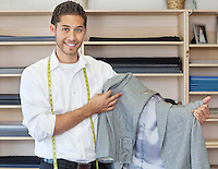 Portrait of handsome young tailor holding custom made suit