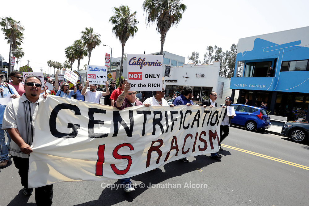 """Protest marchers hold a sign reading """"GENTRIFICATION IS RACISM"""" on Abbot Kinney Bl in Venice, California on May 7, 2015."""