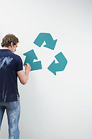 Man painting recycling sign on wall