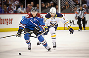 SHOT 3/28/15 9:20:10 PM - The Colorado Avalanche's Tyson Barrie #4 and the Buffalo Sabres' Marcus Foligno #82 chase after a loose puck during their regular season NHL game at the Pepsi Center in Denver, Co. The Avalanche won the game 5-3. (Photo by Marc Piscotty / © 2015)
