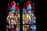 Stained glass window with a prince and princess offered bread and salt on arrival at Marchais castle, 1975, in the Grimaldi Chapel in the Basilica of Liesse Notre Dame, built 1134 in Flamboyant Gothic style by the Chevaliers d'Eppes, then rebuilt in 1384 and enlarged in 1480 and again in the 19th century, Liesse-Notre-Dame, Laon, Picardy, France. Pilgrims flock here to worship the Black Virgin, based on Ismeria, the Soudanese daughter of the sultan of Cairo El-Afdhal, who saved the lives of French knights during the Crusades, converted to christianity and married Robert d'Eppes, son of Guillaume II of France. Picture by Manuel Cohen