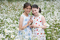 Portrait of two girls (7-9) in meadow full of flowers