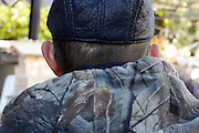 back view of male person wearing a leather flat cap