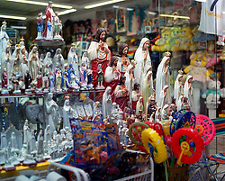 A souvenir shop in Fatima filled with religious figurines alongside childrens toys and games.