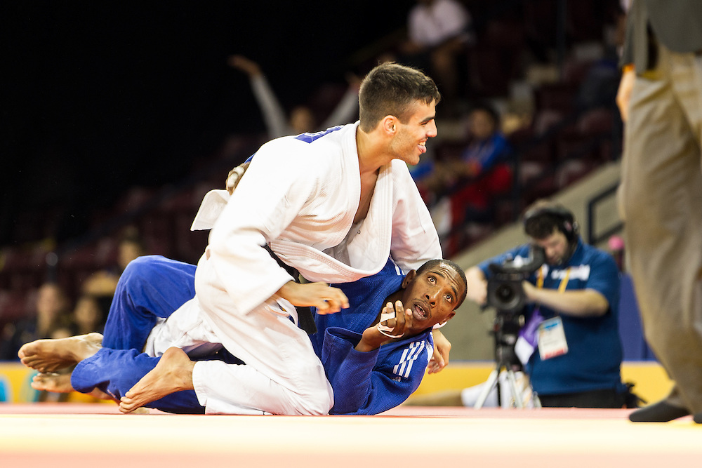 Carlos Tondique (bottom) of Cuba looks to the official after being thrown by Canada's Antoine Bouchard during their final of the table in the 66kg class at the 2015 Pan American Games in Toronto, Canada, July 12,  2015. The throw gave Bouchard the win and a spot in the gold medal contest Sunday evening. AFP PHOTO/GEOFF ROBINS