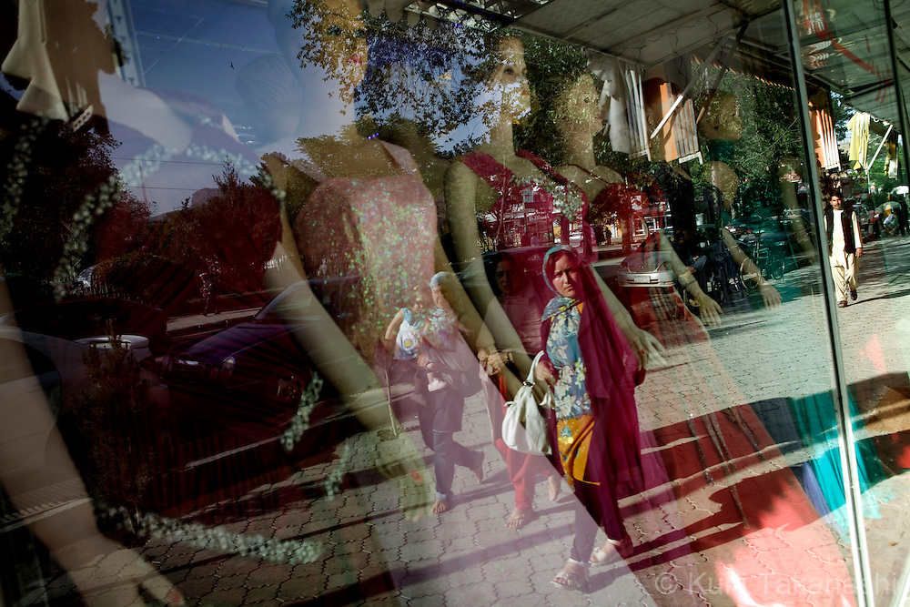 (Kabul Afghanistan - May 17, 2012).Afghan women reflected on the window of female dress shop in Kabul, Afghanistan. Under the mujahideen and the Taliban, women have struggled to gain freedoms and reform a society that is primarily male dominant. .(Photo by Kuni Takahashi)