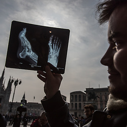 Milan, Italy - 20 March 2015: a man looks at a partial solar eclipse through an X-ray in Piazza Duomo
