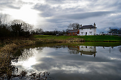 The Lock Keeper's Cottage reflected in the top pound, Foxton Locks, Grand Union Canal, Leicestershire, England.