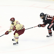Austin Cangelosi #26 of the Boston College Eagles keeps the puck from Zach Aston-Reese #12 of the Northeastern Huskies during The Beanpot Championship Game at TD Garden on February 10, 2014 in Boston, Massachusetts. (Photo by Elan Kawesch)