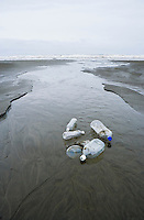 Plastic bottles and lids sitting in a stream as it flows out to the Pacific Ocean.