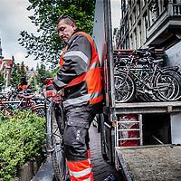 """Nederland, Amsterdam, 24 juni 2016.<br /> Elke maand organiseerde het Fietsdepot voor professionele opkopers een veiling van de fietsen die niet binnen zes weken zijn opgehaald door hun eigenaar. Maandagochtend vindt voor de laatste keer een fietsveiling plaats. Voor die speciale gelegenheid neemt wethouder Pieter Litjens (Verkeer) de veilinghamer ter hand.<br /> Vanaf 1 juli is het Haarlemse bedrijf TradeFRM verantwoordelijk voor de verkoop van niet-opgehaalde fietsen aan handelaren en aan socialewerkprojecten. """"Ook het niet verkoopbare materiaal zal door TradeFRM op de meest duurzame manier worden gerecycled en hergebruikt,"""" aldus de gemeente.<br /> Alle door de gemeente weggeknipte fietsen komen terecht op het terrein van het Fietsdepot in het Westelijk Havengebied. Amsterdammers kunnen daar terecht om hun weggeknipte fiets weer op te halen. Dat kost sinds 1 januari dit jaar 22,50 euro. Daarvoor was dat 15 euro. Thuis laten bezorgen kan ook, voor 50 euro. Iets minder dan de helft van de fietsen worden door de eigenaar opgehaald.<br /> Op de foto: Fietsen die te lang langs de grachten blijven staan worden door de Gemeente weggesleept.<br /> VOORKEURFOTO!<br /> <br /> <br /> Foto: Jean-Pierre Jans"""