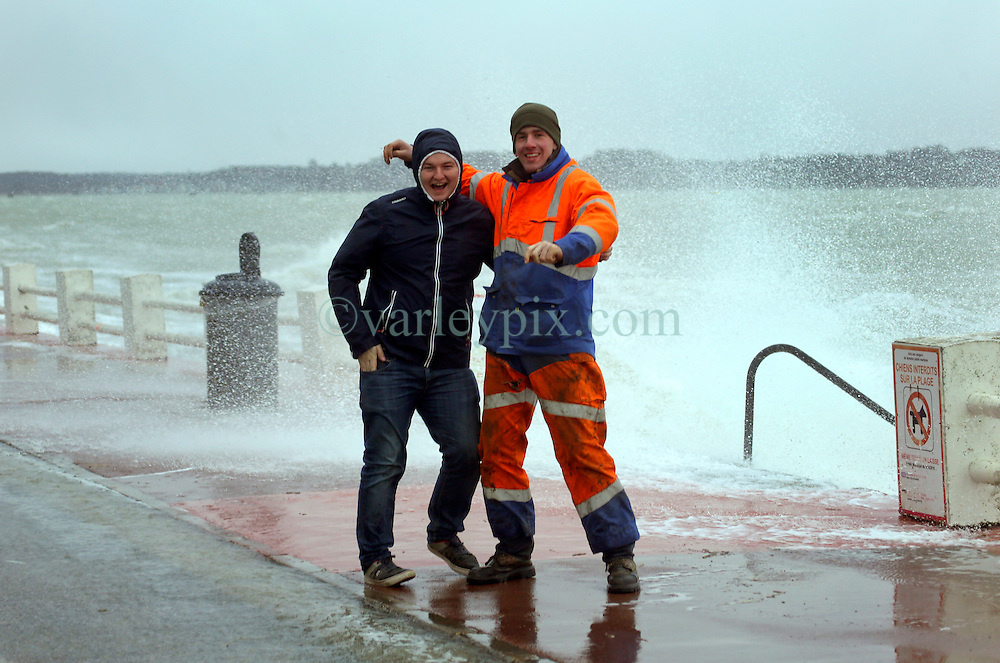 13 Jan 2017. Le Crotoy, Picardie, France.<br /> Friends stand in the spray as waves from a fierce winter storm pushes the tide over the surge barrier on the Promenade Jules Noiret in the Bai Somme.<br /> Photo©; Charlie Varley/varleypix.com