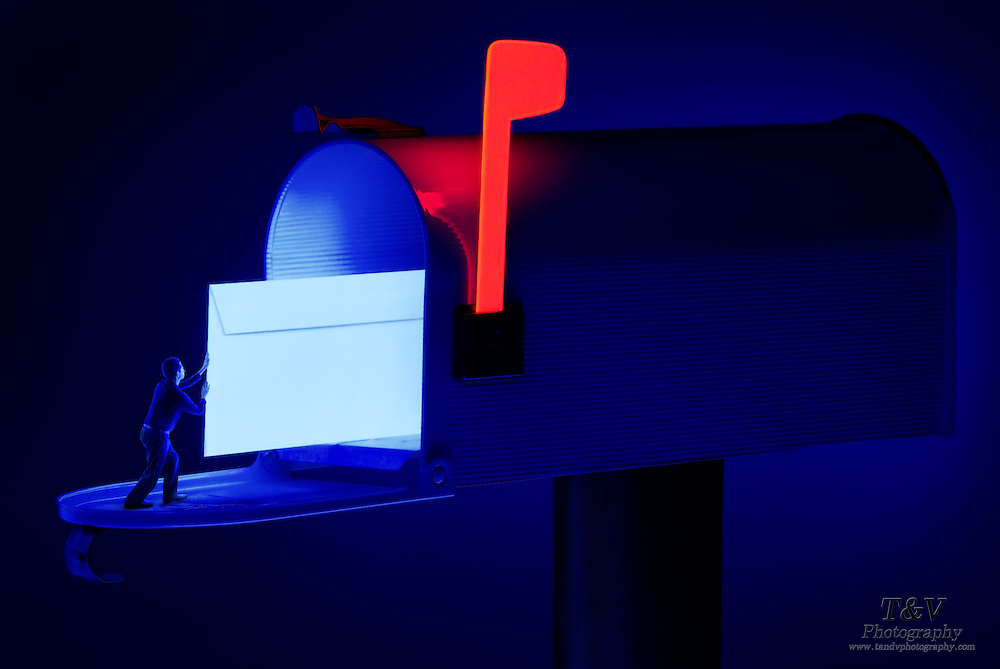 A minature man pushes a glowing envelope into an open mailbox.Black light