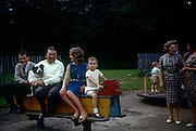 Family and friends sit on a rocking horse in a playground during summer time in the early 1960s. The portrait has been recorded on a film camera by the boy at the front's father, an amateur photographer in 1961. A man is holding on tight to a black and white pet sheepdog and two mothers chat on the right of the picture in this public park in Kent. The picture shows us a memory of nostalgia in an era from the last century.