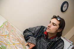Young Czech Man sitting at kitchen table studying city map,
