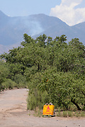 A lightening caused forest fire is monitored in the early stages by Coronado National Forest officials in Sawmill Canyon, Santa Rita Mountains northwest of Sonoita, Arizona, USA. A sign irestricting campfires notes fire restrictions in the area.
