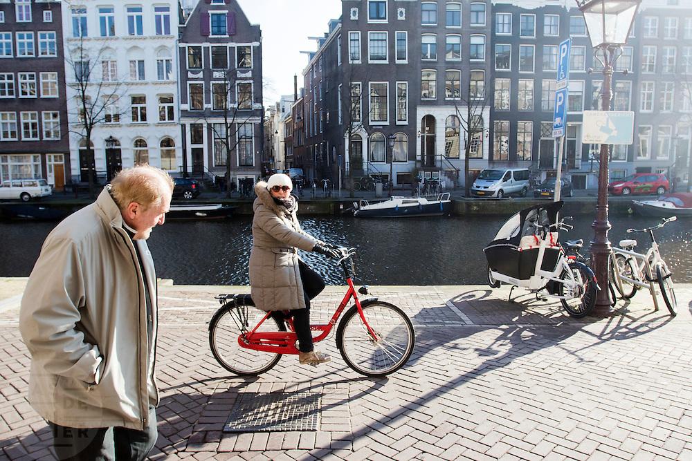In Amsterdam rijdt een touriste op een huurfiets over de Kloveniersburgwal.<br /> <br /> In Amsterdam a tourist is riding on a rental bike at the Kloveniersburgwal.