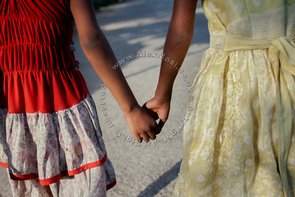 Poonam, 10, (left) and her older sister Jyoti, 11, are walking hand in hand near their newly built home in Oriya Basti, one of the water-contaminated colonies in Bhopal, central India, near the abandoned Union Carbide (now DOW Chemical) industrial complex, site of the infamous '1984 Gas Disaster'.