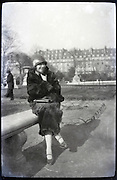 female person wearing fur coat in park Paris 1900s
