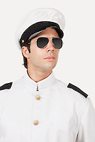 Young navy officer wearing glasses against gray background