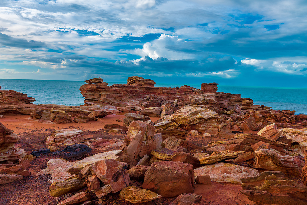Dramatic red rock formation with blue sky and Indian Ocean in the background