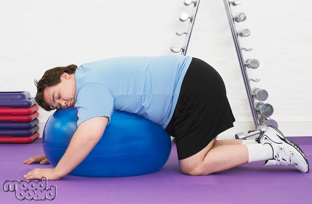 Overweight Man sleeping on Exercise Ball in health club